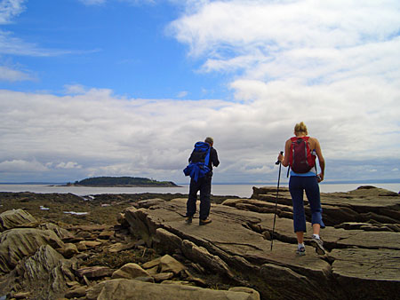 pair of hikers in Mary's Point, New Brunswick, overlooking Grindstone Island in the Bay of Fundy