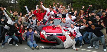 university students surrounding red Saturn Astra